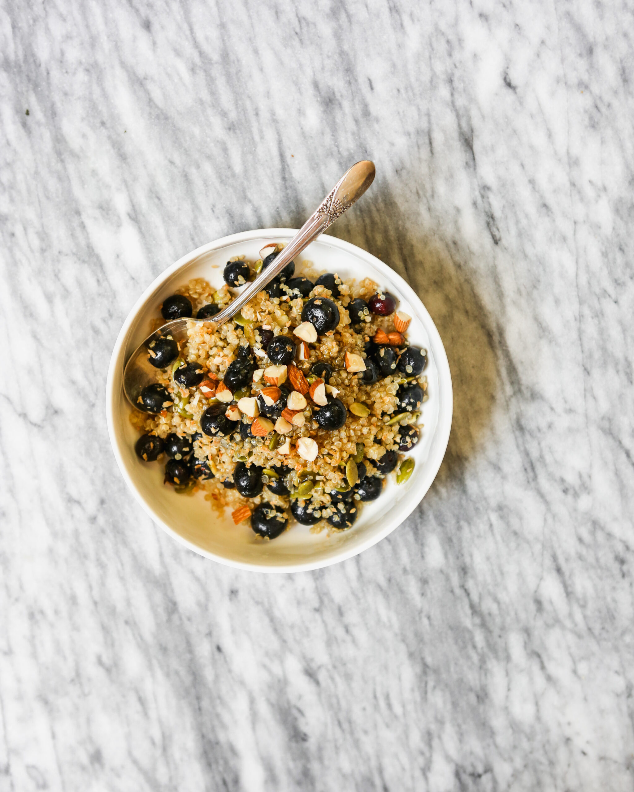 A bowl of breakfast quinoa set on a marble surface.