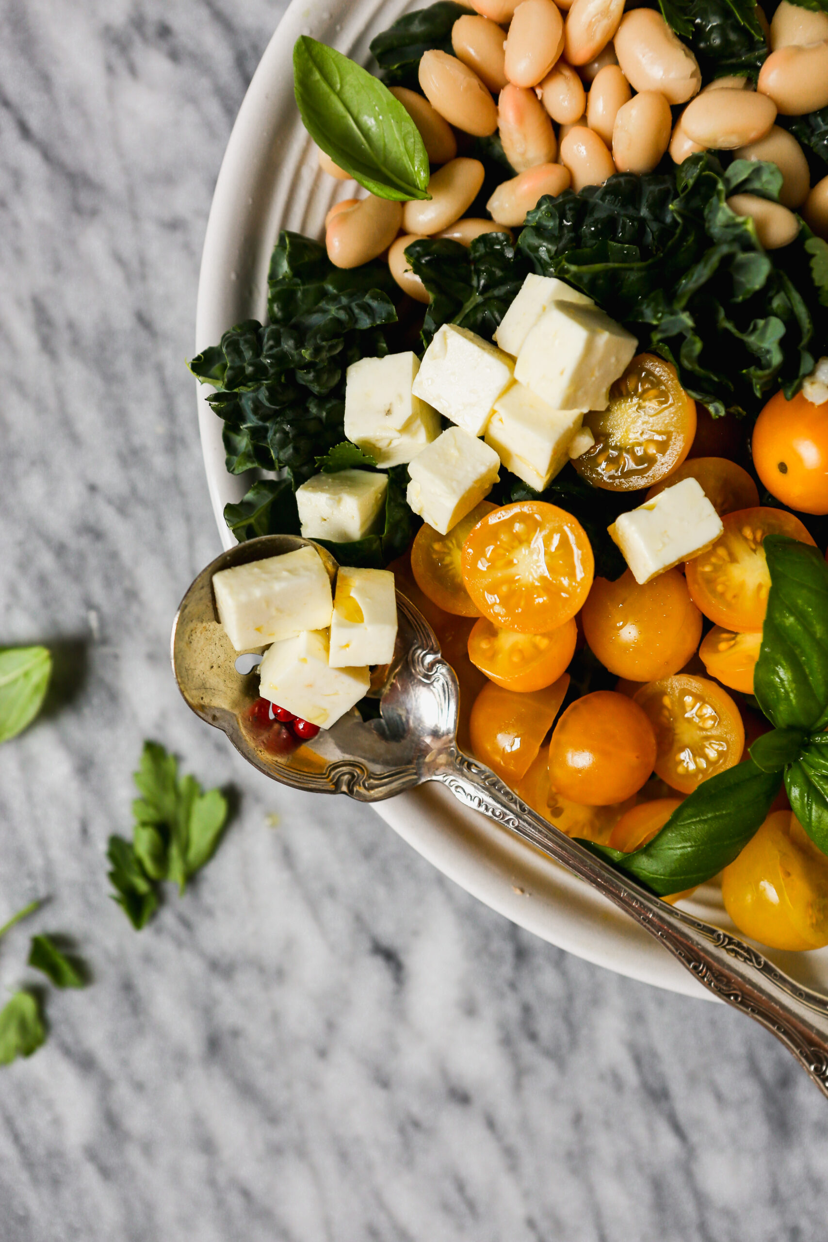 Kale and Sorghum Salad with yellow tomatoes, basil, cucumbers, white beans, and feta in a white bowl on a marble surface.