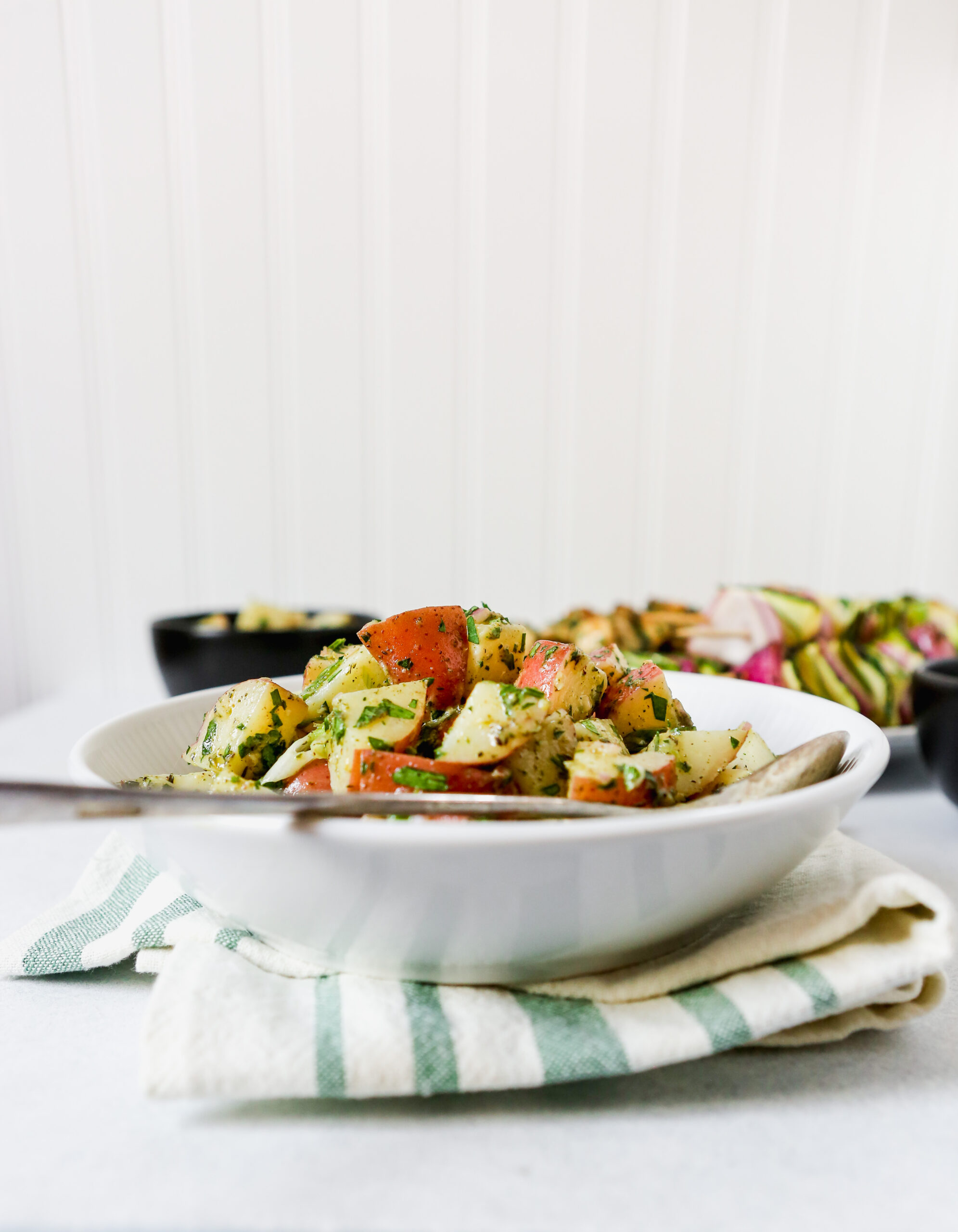 White bowl of Asian potato salad set on a green and white kitchen towel. Food photography