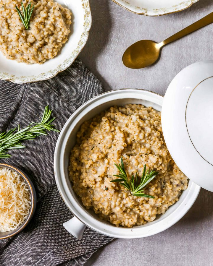 A white and gold bowl, filled with a serving or sorghum risotto and garnished with a sprig of rosemary