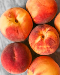 Vibrant peaches clustered together on a marble surface.
