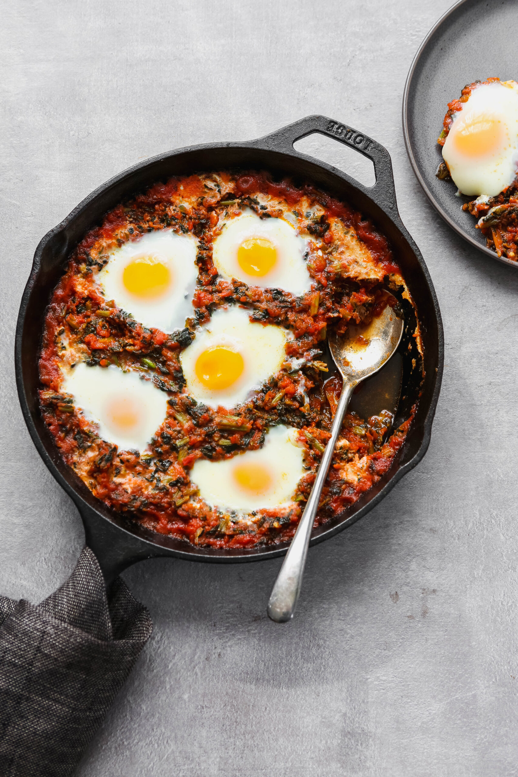 Baked eggs in tomato sauce in a cast-iron skillet.