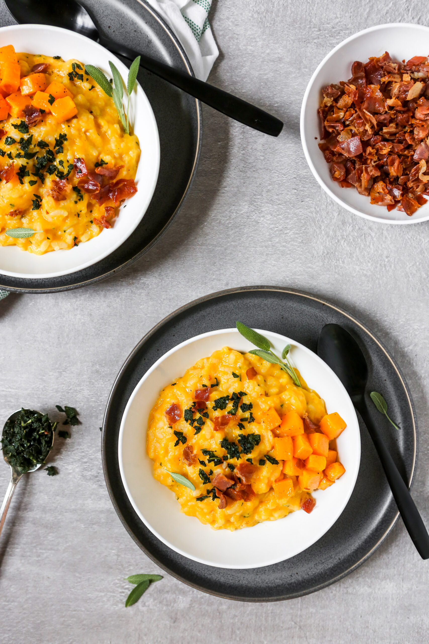 orange risotto in a white bowl set on a gray plate