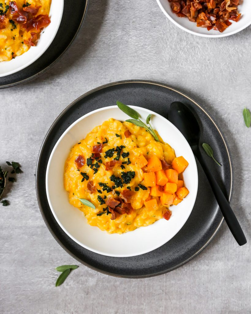 butternut squash risotto in a white bowl set on a gray plate