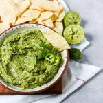 A large bowl of guacamole set on a cutting board with corn chips.
