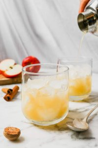 Apple bourbon cocktail on a white marble surface garnished with apple slices and cinnamon stick