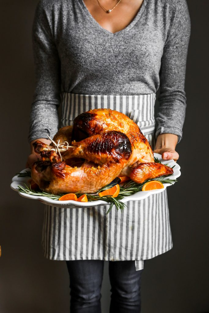 photograph of a whole glazed roast turkey on a large white platter held by someone in an apron