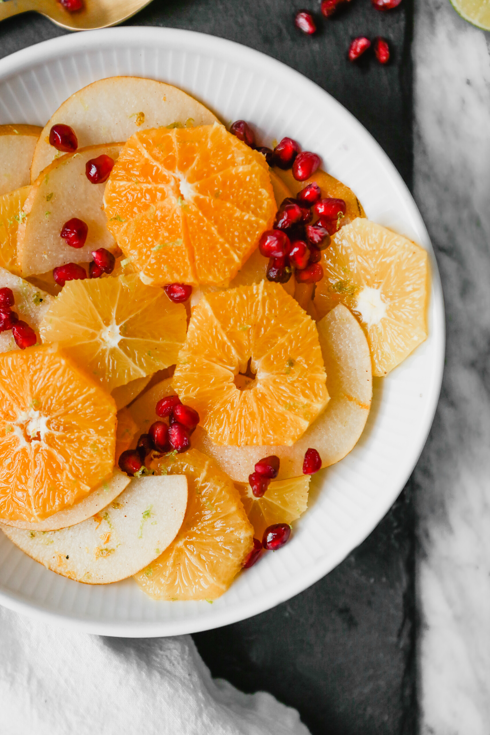 Photograph of winter citrus fruit salad with pomegranate seeds set in a white bowl on a marble table.