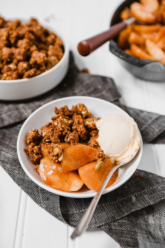 Photograph of healthy apple crisp in a white bowl on a white table