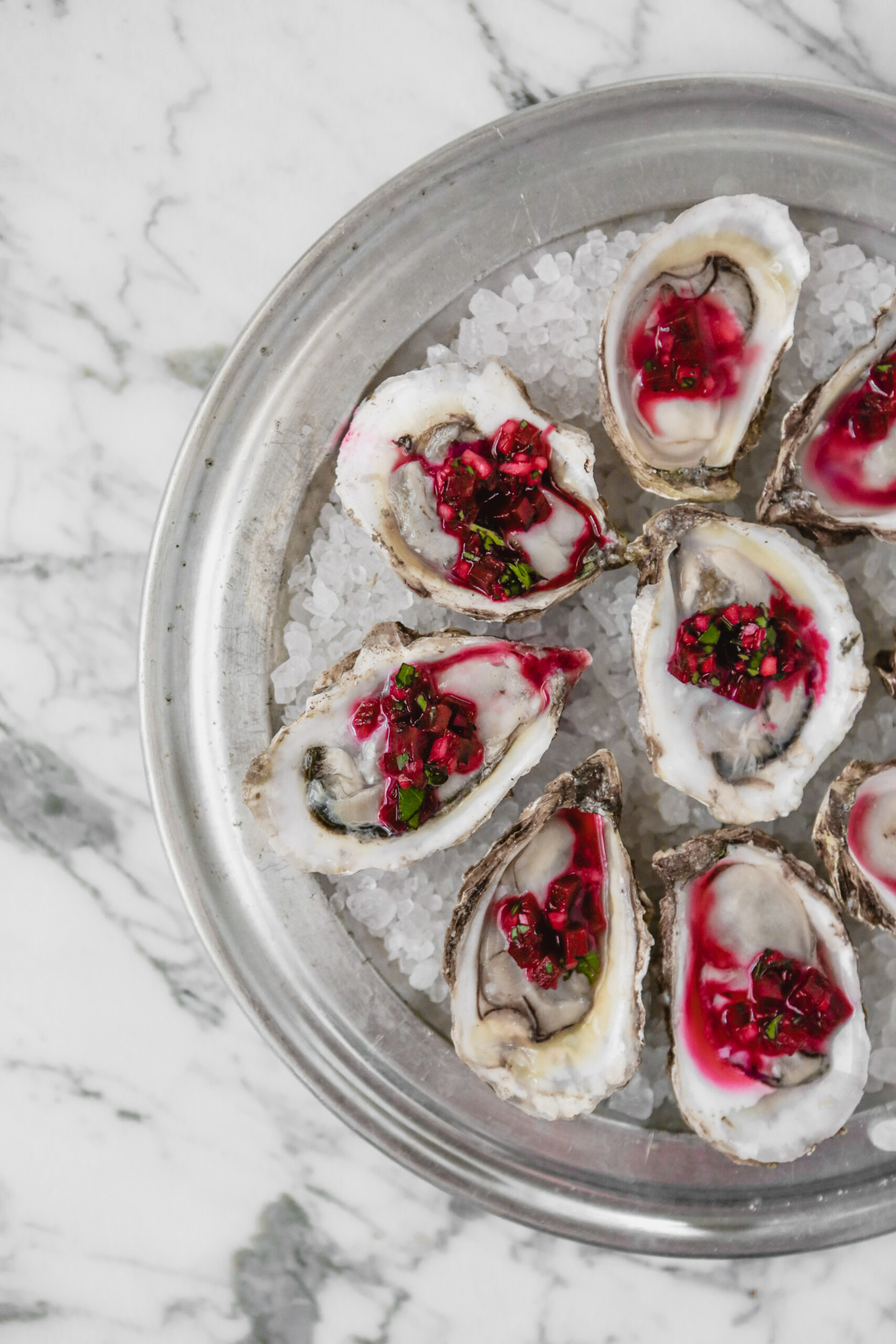 Photograph of oysters on the half shell set on rock salt in a metal pan on a marble surface, topped with a red mignonette sauce.