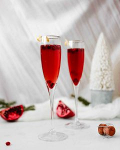 Photograph of pomegranate kir royale cocktail in two flutes, cheersing