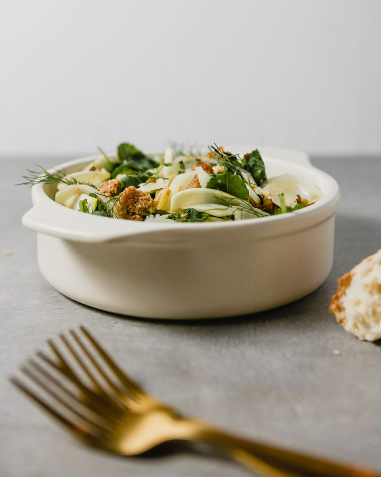 Photograph of fennel salad in a white serving dish with gold serving utensils. .