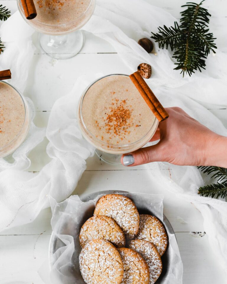Photograph of homemade eggnog cookies and homemade vegan eggnog set on a white wooden table with evergreens