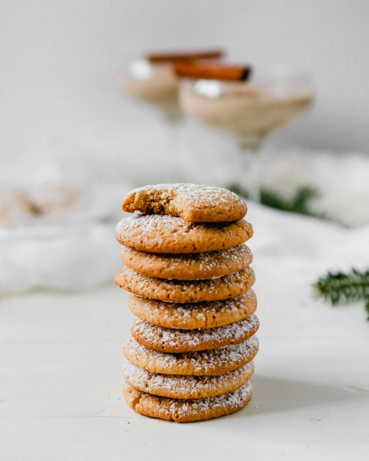 Photograph of eggnog cookies stacked on top of eachother with eggnog in the background.