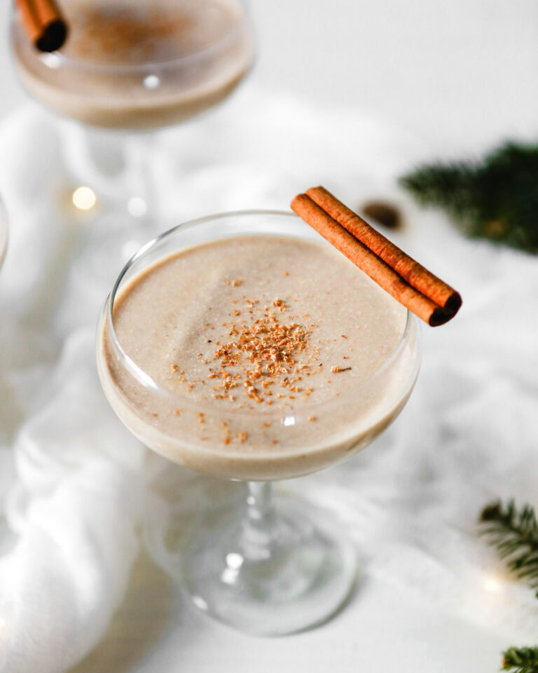 Photograph of homemade eggnog in a coupr glass set on a white wooden table.