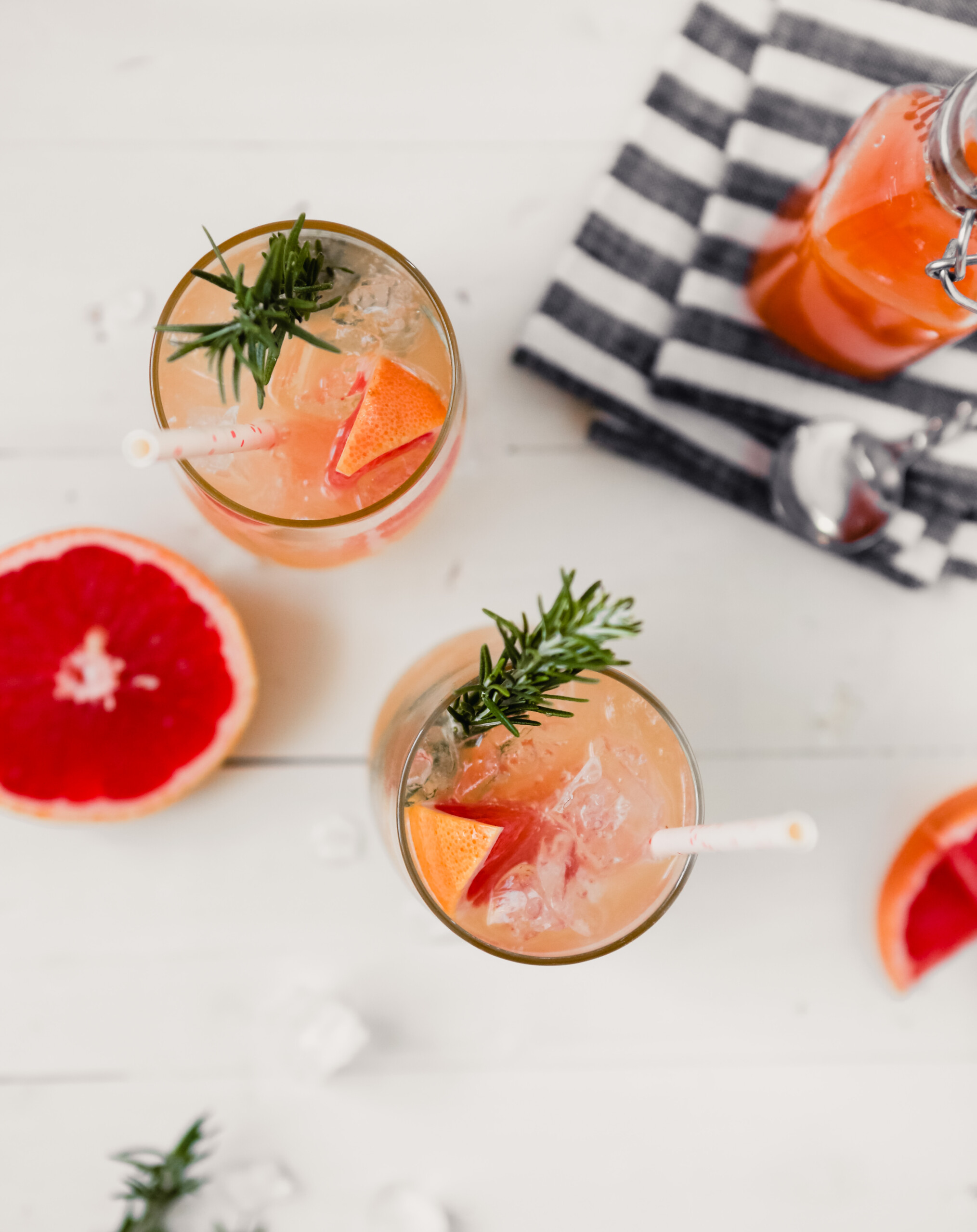 Photograph of a homemade grapefruit soda with a grapefruit slice, sprig of rosemary and white straw