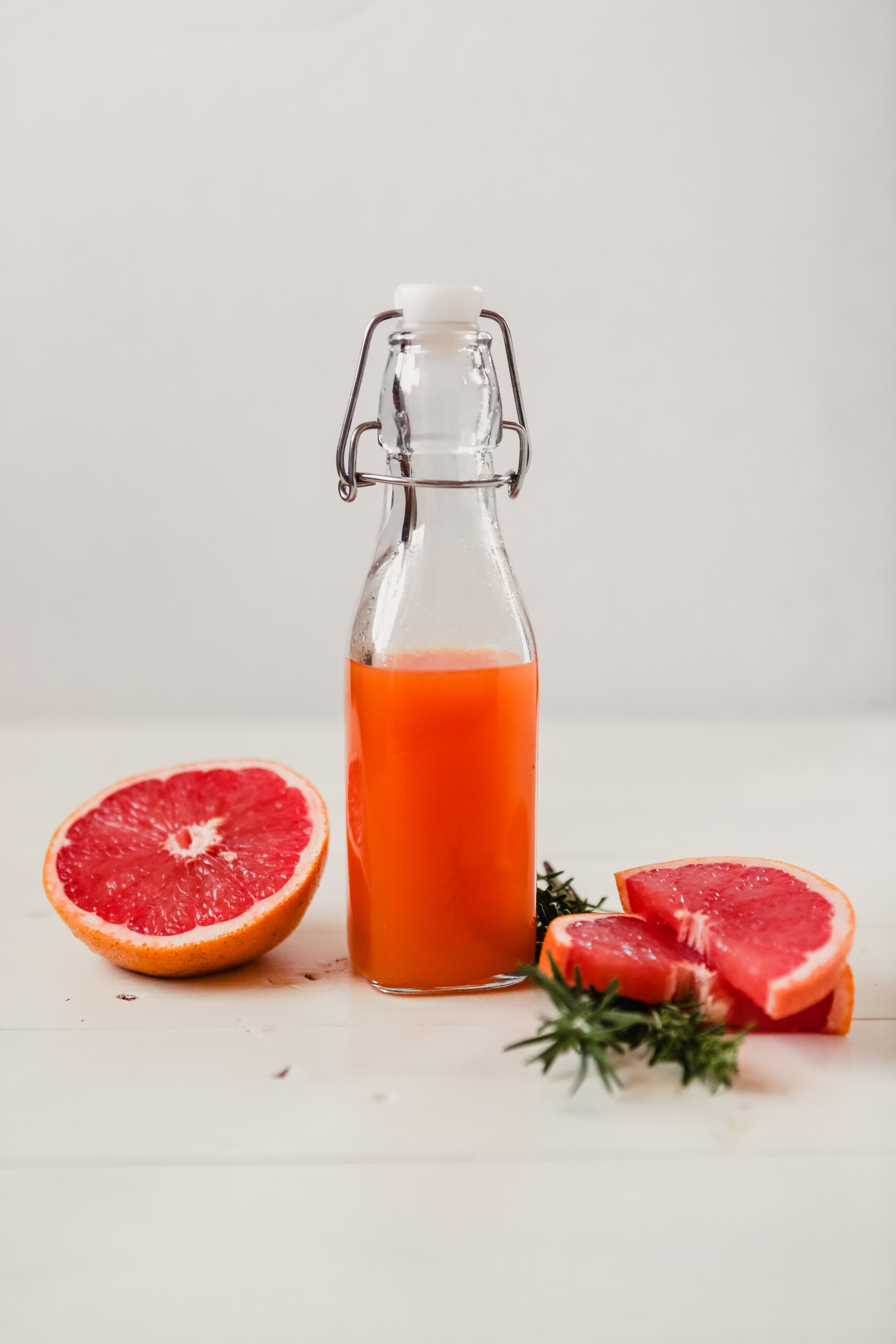 Photograph of homemade grapefruit soda syrup in a glass bottle.