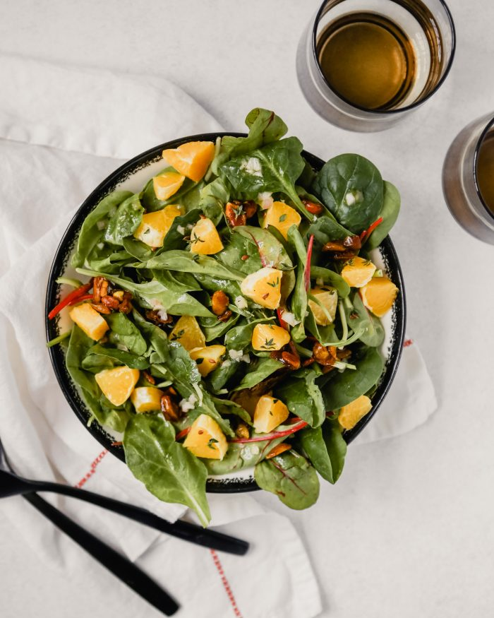 Photograph of a big bowl of winter green salad with diced oranges, fresh thyme and candied pistachios