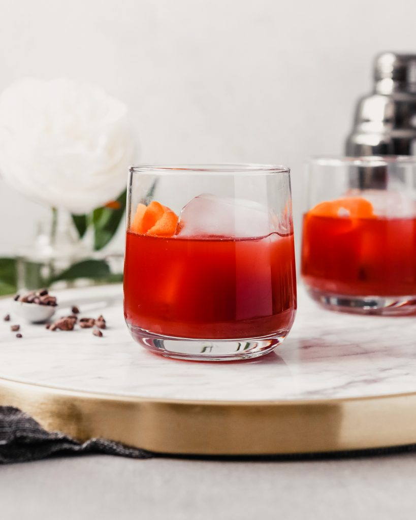 Photograph of a negroni cocktail in a rocks glass set on a white marble tray.