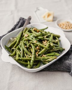 Roasted green beans with pine nuts in a square white serving dish. Parmesan and pine nuts in the background