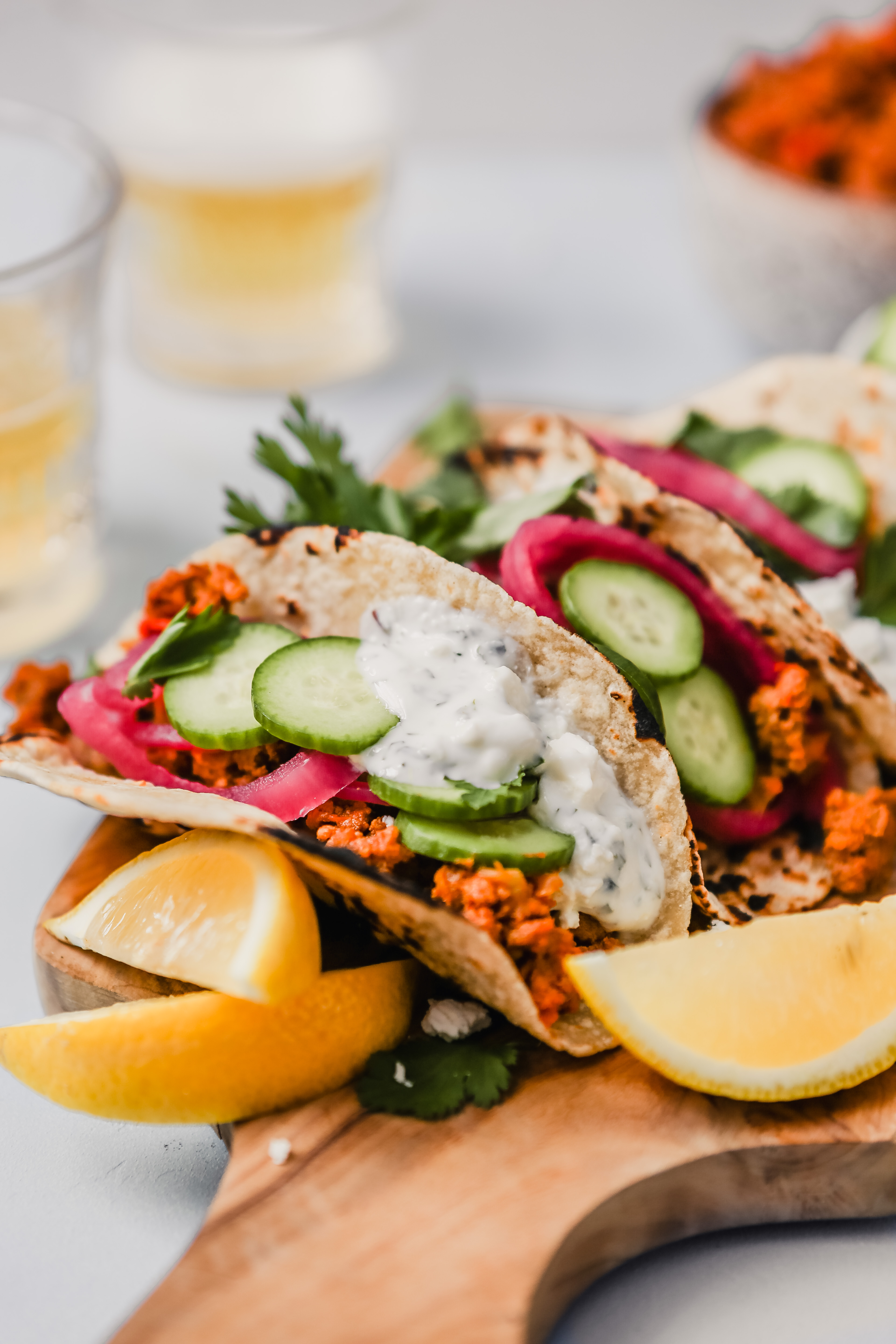 Photograph of three lamb tacos arranged on a wooden cutting board with lemon wedges and cucumber slices.