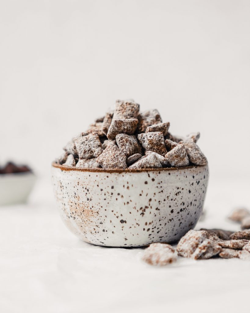 Photograph of healthy puppy chow piled into a spotted pottery bowl on a white table.