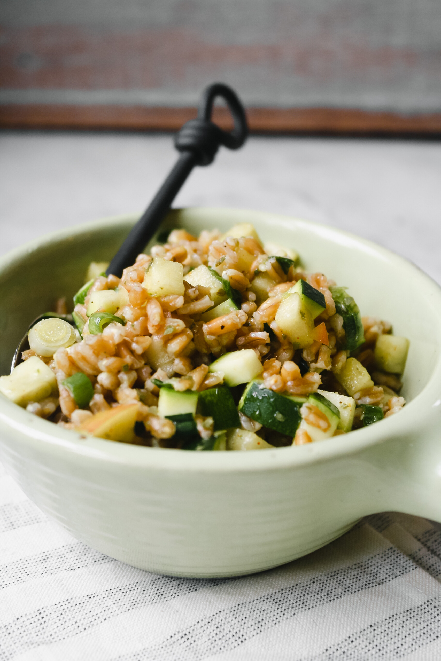 Overhead photograph of farro salad in a greed bowl on a white marble table