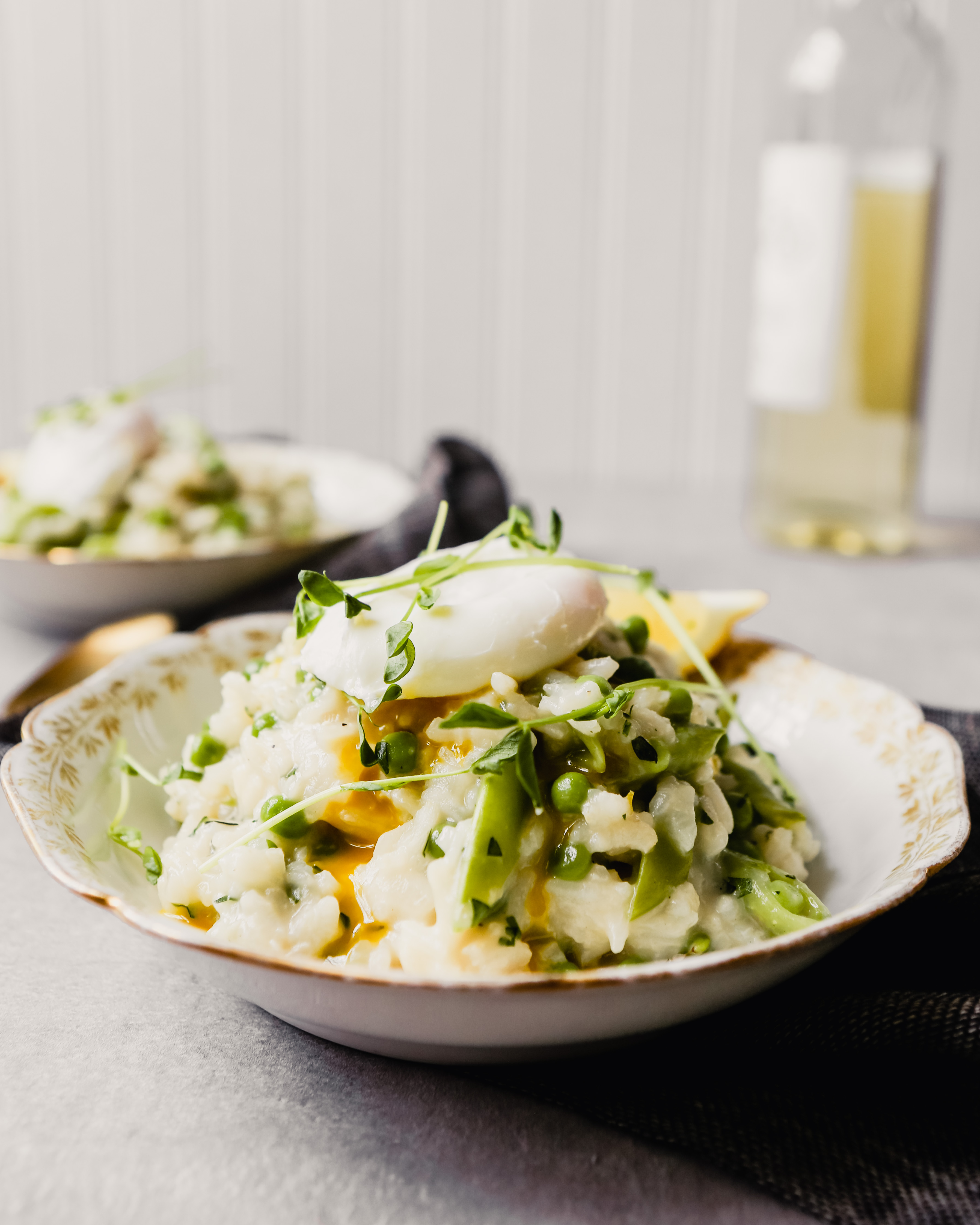 Photograph of spring risotto made with peas, snap peas and topped with pea shoots and a poached egg
