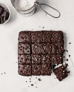 Photograph of a batch of brownies on a white surface cut into squares and dusted with powdered sugar
