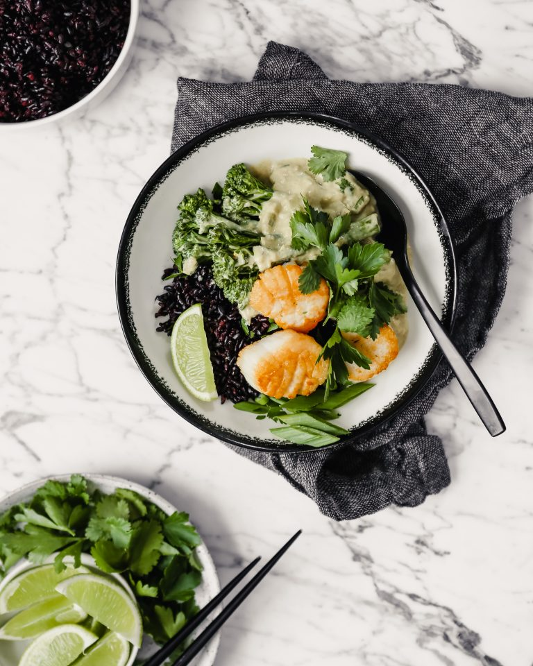 Photograph of a bowl filled with green coconut curry, black rice, broccolini and golden scallops set on a marble table with a gray napkin.