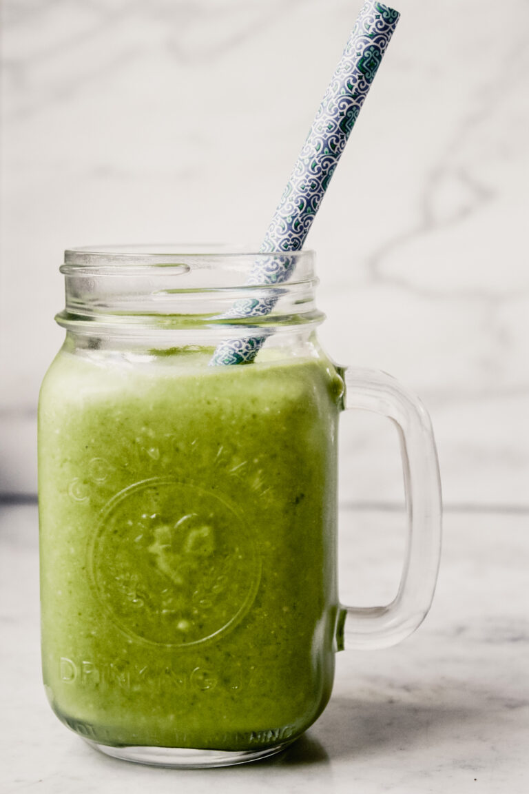 Photograph of a green kale smoothie in a glass Ball jar with a blue straw