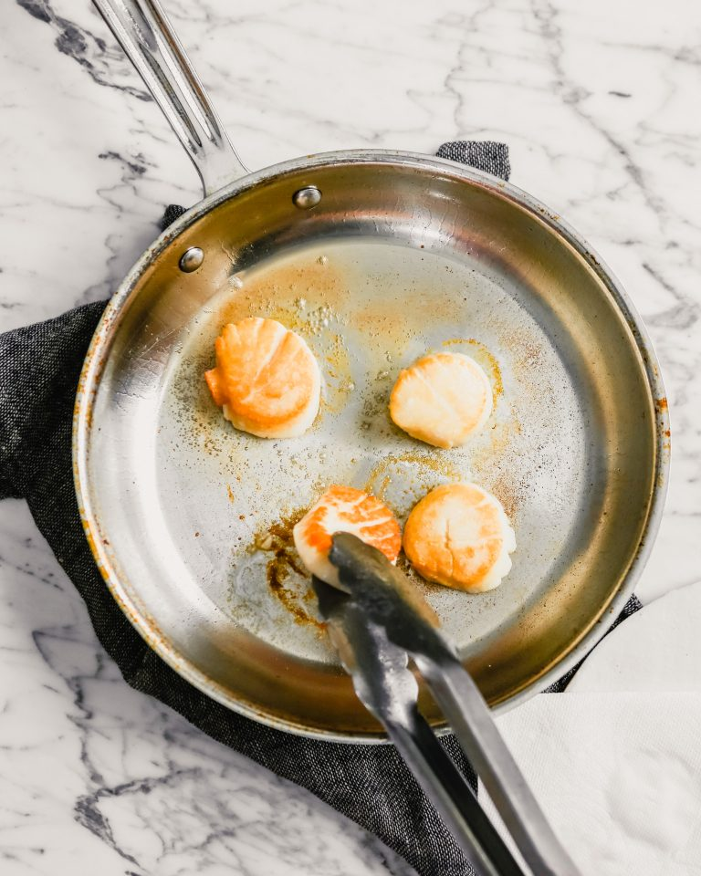 Photograph of golden brown scallops searing in a skillet.