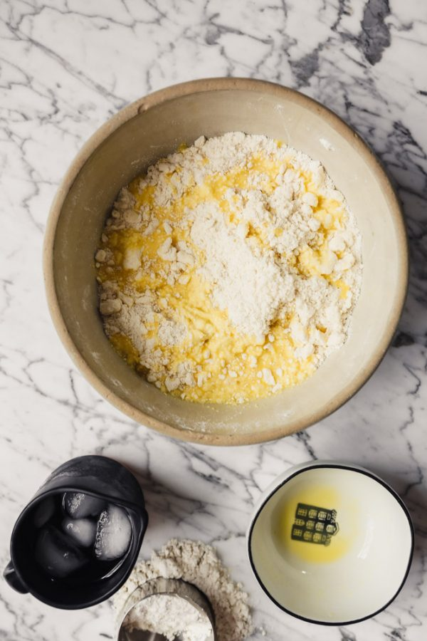 Photograph of a large bowl filled with gluten-free flour with egg poured over top
