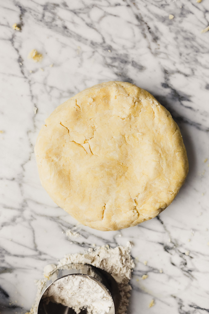 Photograph of a disk of gluten-free dough set on a white marble table.