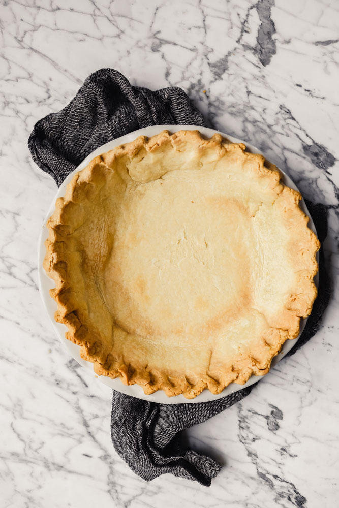 Photograph of a pie plate lined with a baked pie shell set on a white marble table