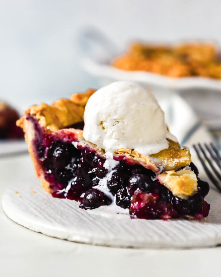 slice of blueberry pie set on a white plate with a scoop of vanilla ice cream on top and melting down the slice