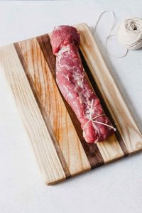 Photograph of a pork tenderloin tied with kitchen twine