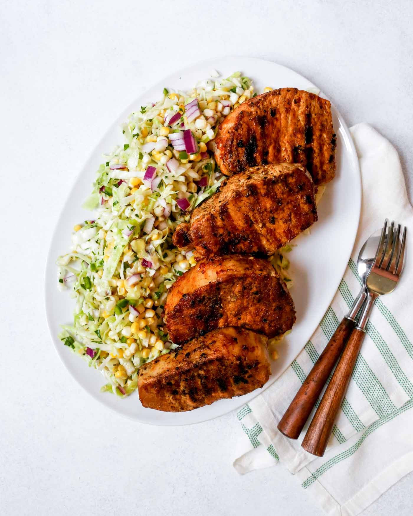 Photograph of grilled boneless pork chops on a white platter with sweet corn slaw.