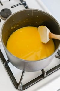 Photograph of lemon curd being cooked on the stove top with a white spatula