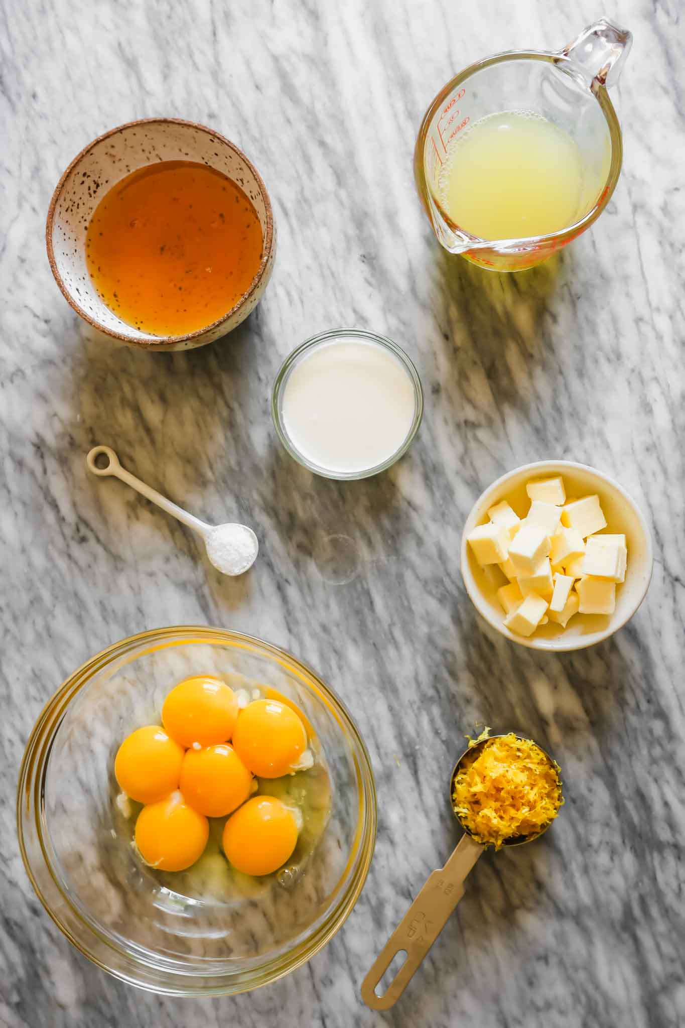 Overhead photograph of lemon curd ingredients set on a marble table