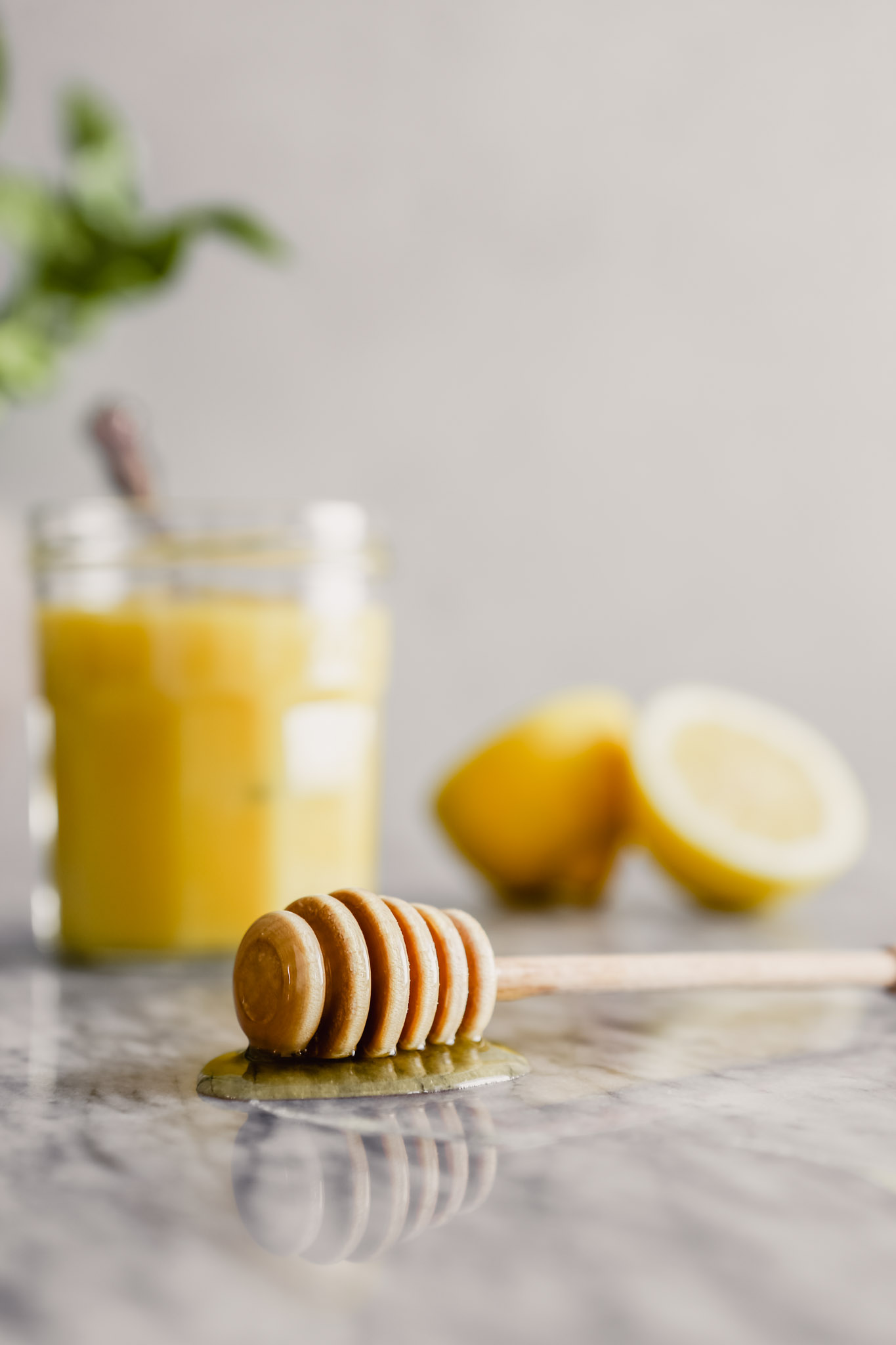 Photograph of a honey dipper let on a marble table with lemon curd set in the background
