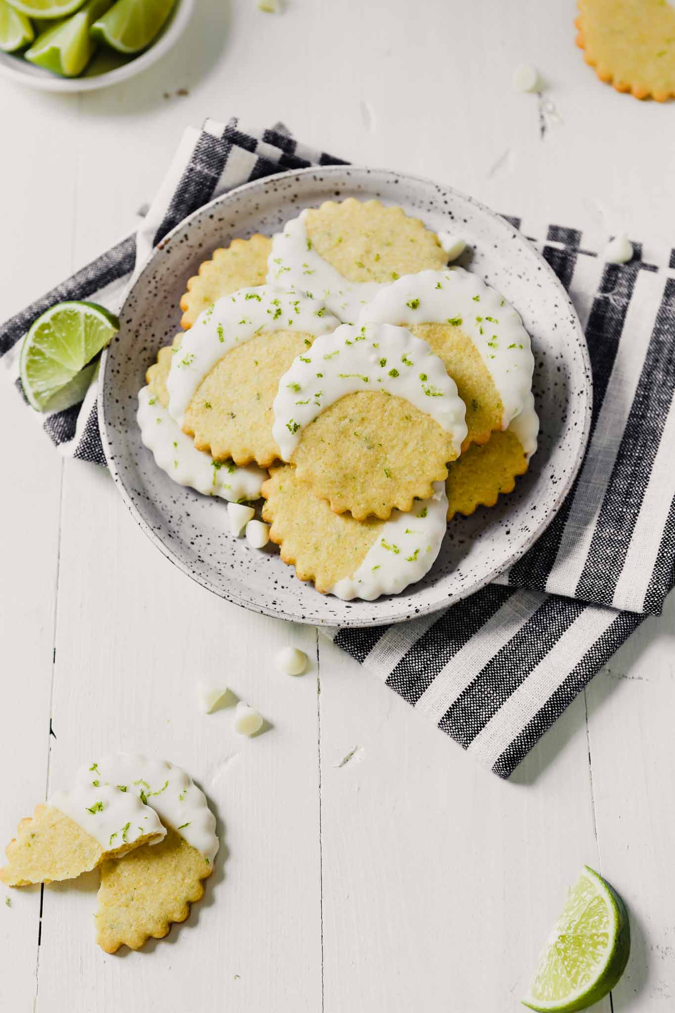 Photograph of glazed cornmeal cookies stacked on a speckled plate on a white table with limes scattered about