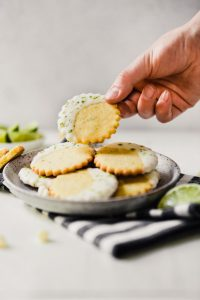 Photograph of glazed cornmeal cookies stacked on a speckled plate one being taken off by someone, set on a white table with limes scattered about