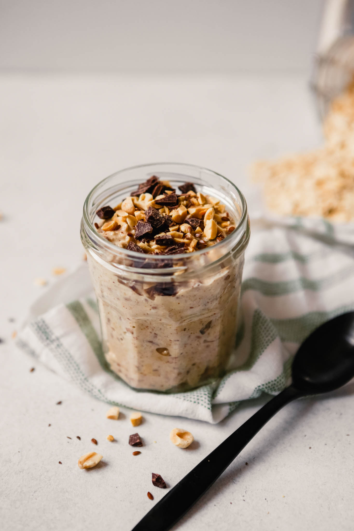 Photograph of chocolate peanut butter overnight oats in a glass jar on a table with spilled oats