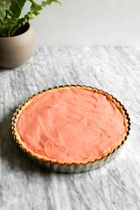 Photograph of a tart crust filled with rhubarb curd set on a marble table.