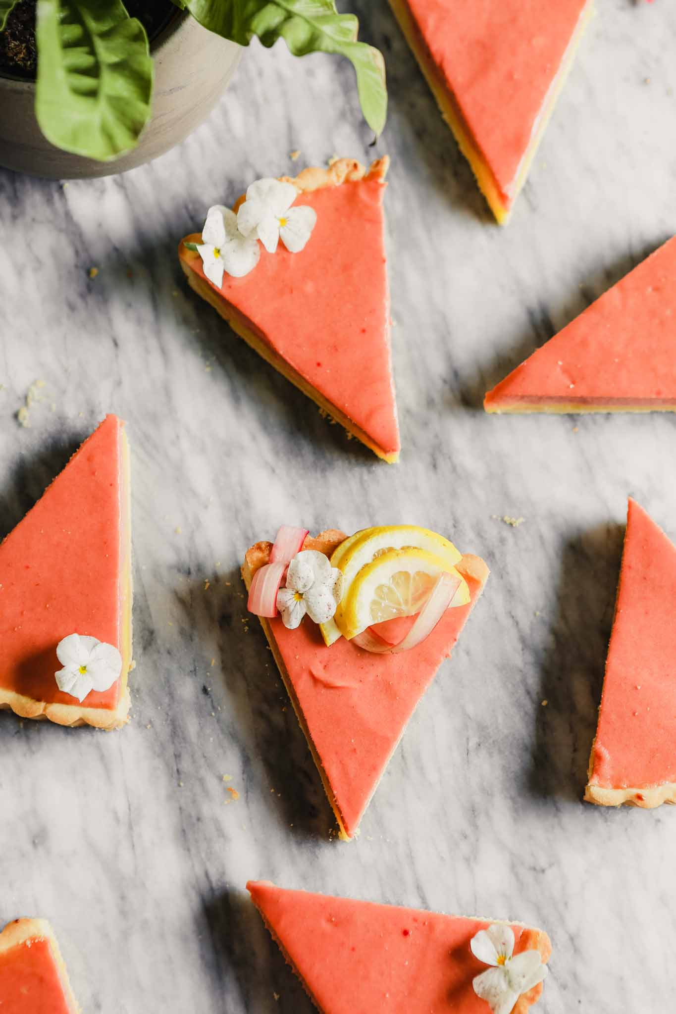 Overhead photograph of wedges of layered rhubarb tart set on a marble table.