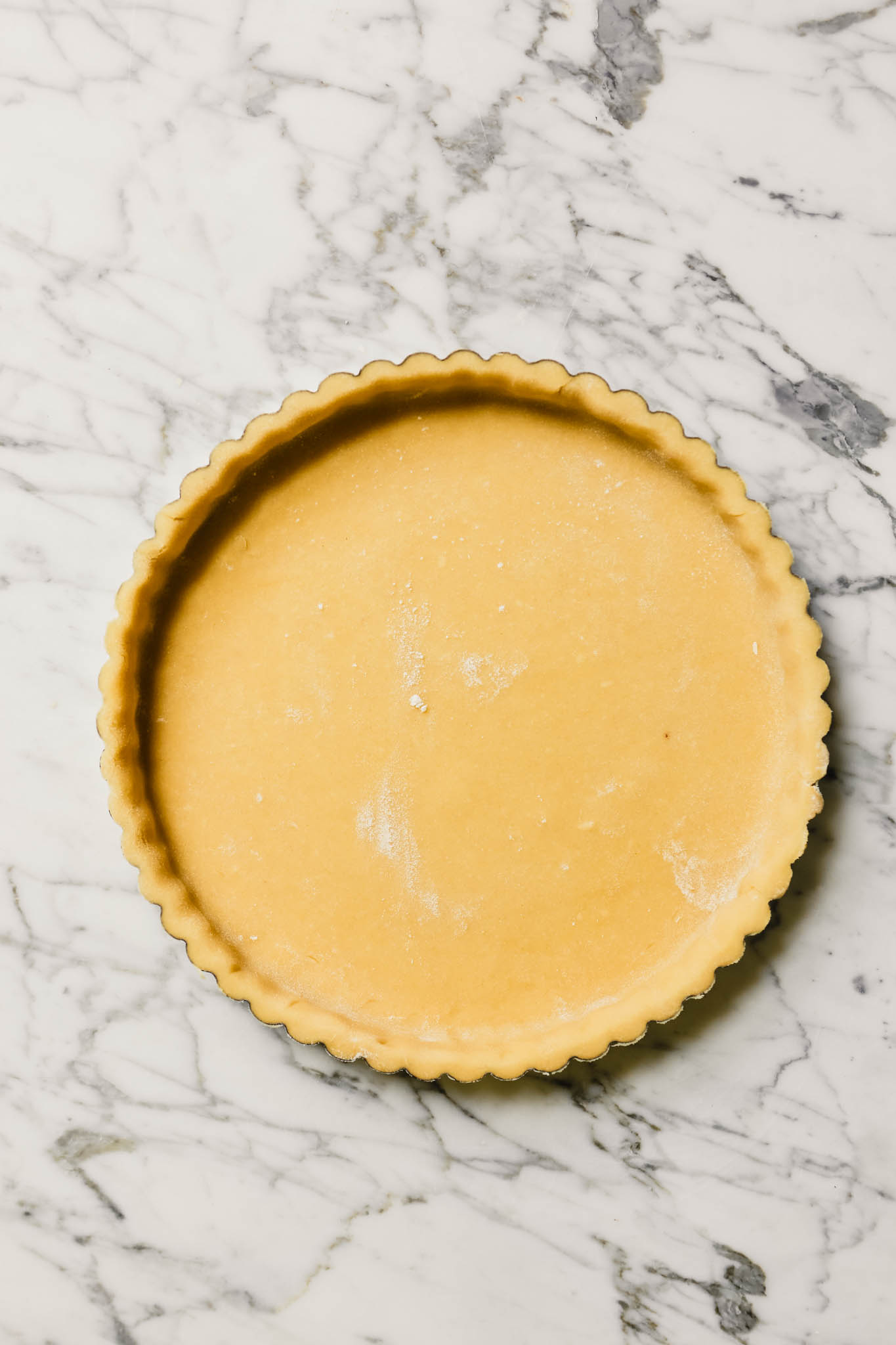 Photograph of an unbaked tart shell in a tart pan set on a marble table.