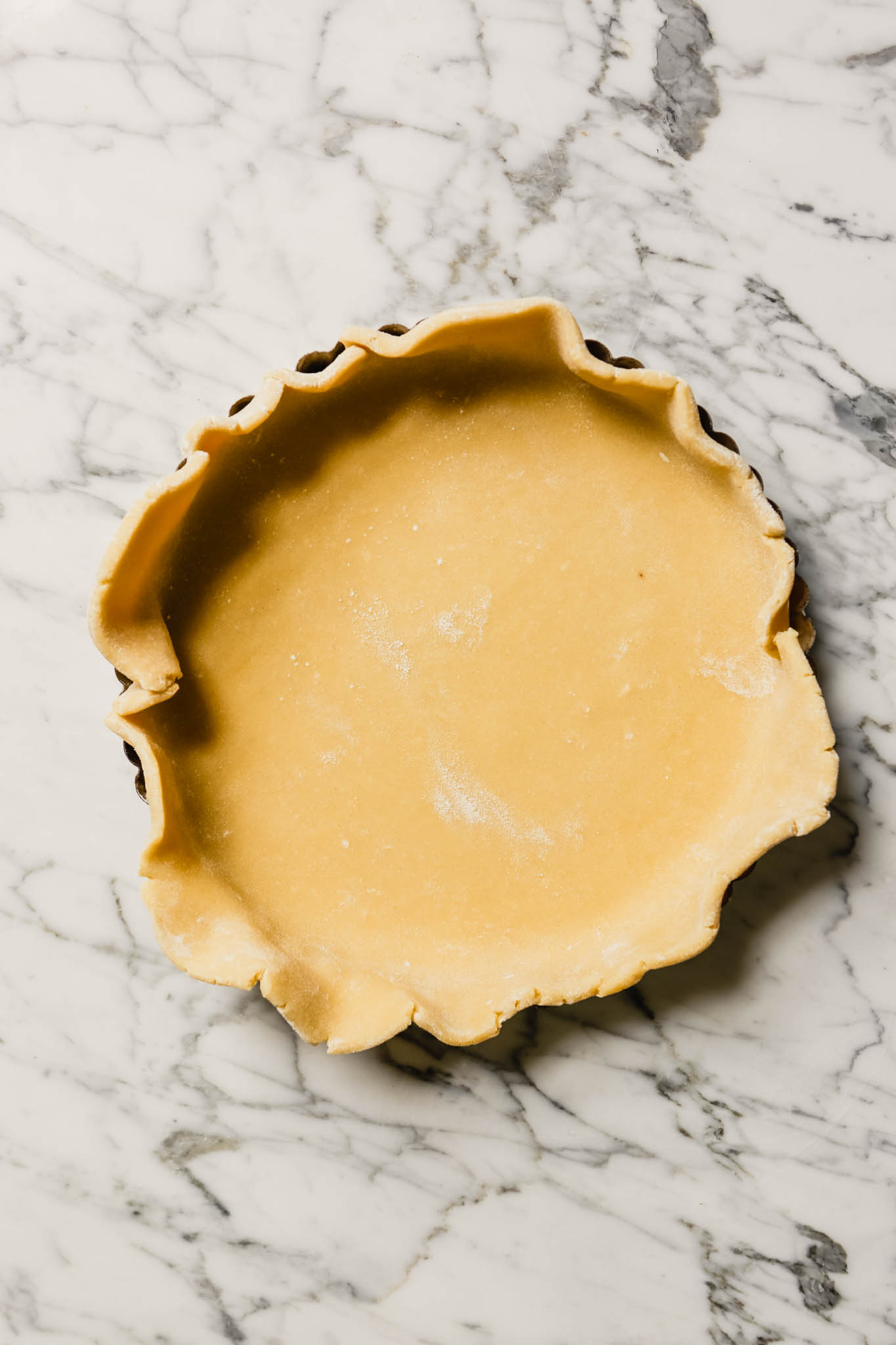 Photograph of dough placed in a tart pan set on a marble table.
