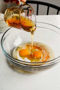 Photograph of honey being poured into a bowl with brown butter, buttermilk and eggs