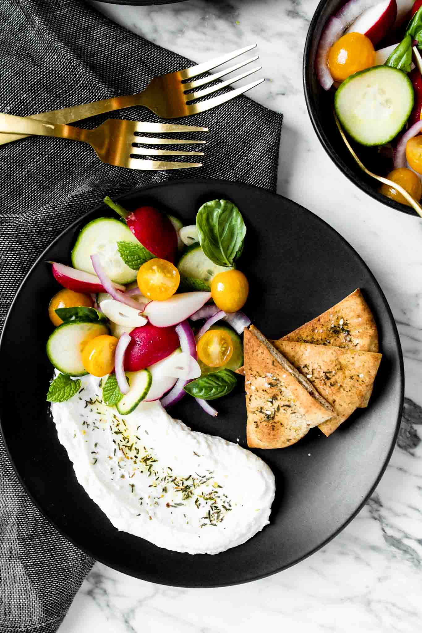Photograph of homemade labneh on a plate with toasted pita bread and summer vegetables